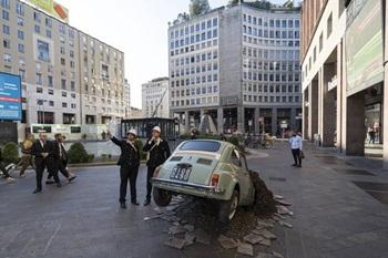 Una Fiat 500 piantata nel terreno in Piazza San Babila